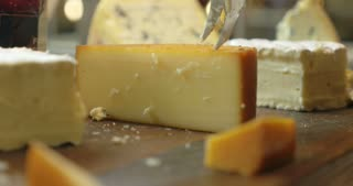 Closeup shot of a piece of cheese. Somebody is cutting a serving of it with a knife.