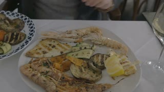 Closeup shot of a plate with grilled seafood and vegetables on the table. Female hand is squeezing lemon over the food and taking photo on the smartphone.