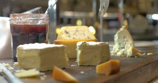 Closeup shot of a soft cheese on wooden board being cut with a knife. A jar of jam is standing nearby.