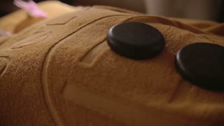 Closeup shot of massaging hot stones lying on the body. Massagist is turning them.
