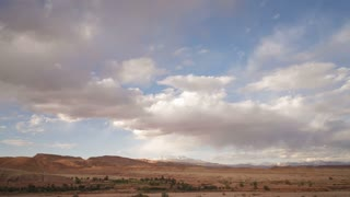 Cloud formations over the Atlas mountains near the ancient Kasbah town of Ait Benhaddou beside the Quarzazate River, Morocco, North Africa, T/Lapse