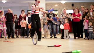 Clown riding a unicycle in Akvamarine circus. A unicycle is a human-powered, single-track vehicle with one wheel. The event took place on November 11, 2012 in Moscow, Russia.