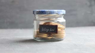 College Fund Money Jar. A clear glass jar filed with coins, saving money.