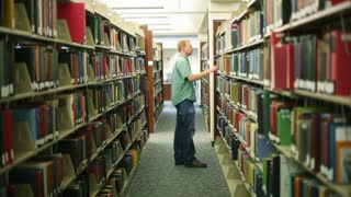College Student Looks At Library Book