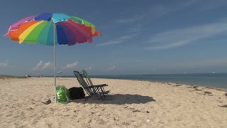 Colorful Beach Chairs and Umbrella on Beach