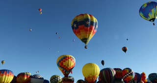 Colorful hot air balloons floating over head on bright sunny day