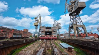 Construction of the ship in shipyard timelapse with cranes. Blue cloudy sky