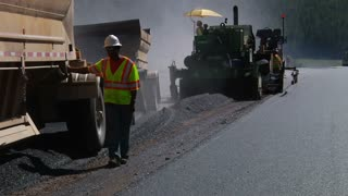 Construction Team And Machines Laying Asphalt