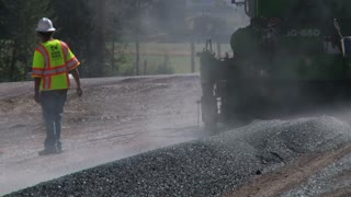 Construction Team Flattening New Asphalt