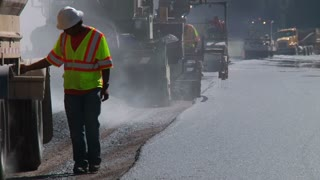 Construction Team Laying Asphalt