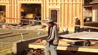 Construction Worker Carries Lumber