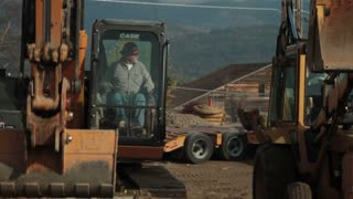 Construction Worker Operates Excavator