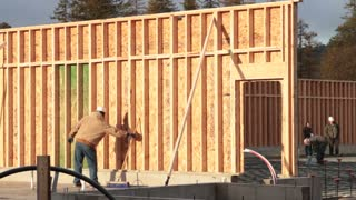 Construction Worker Walks Along Newly Built Wall
