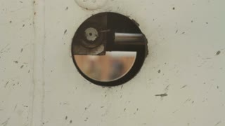 Construction Workers Seen Through Metal Hole Rack Focus