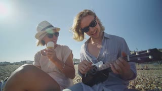 Cool couple on a beach having fun with a ukulele and ice cream