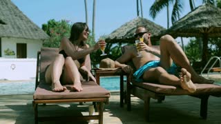 Couple drinking cocktails and relaxing, steadycam shot