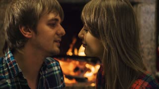Couple kissing by the fireplace. Romantic cozy night by the fireplace. 4k graded from RAW, UHD, Ultra HD resolution.