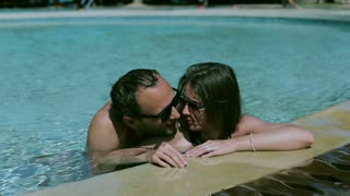 Couple kissing in the pool, steadycam shot