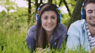 Couple listening to music and smiling in summer on headphones while hanging out in park.