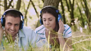 Couple listening to music in summer on headphones while hanging out in park.