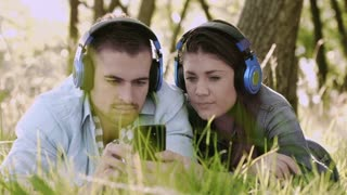 Couple listening to music/ selecting songs on smart-phone in summer on headphones while hanging out in park.
