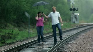 Couple Playfully Walking on Train Tracks