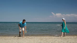 Couple playing bat and ball tennis game at the beach on the golden sand at the edge of a calm ocean as they enjoy their summer vacation