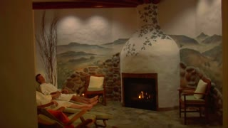 Couple Relaxes In European Spa With Fireplace