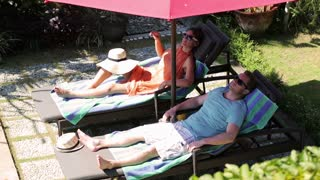 Couple relaxing on sunbeds