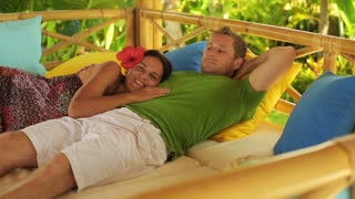 Couple resting on bed in the garden and smiling to the camera, steadycam shot