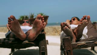 Couple resting on sunbeds, steadycam shot