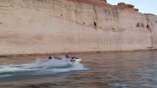 Couple Ride Jet Skis In Slow Motion With Red Rock Cliffs
