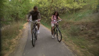 Couple Riding Bikes Through Tree Covered Path 3