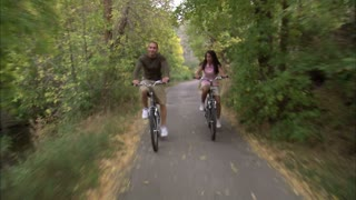 Couple Riding Bikes Through Tree Covered Path 5