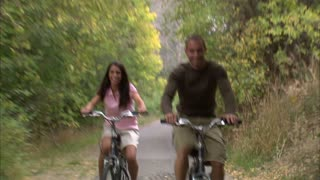 Couple Riding Bikes Through Tree Covered Path 7