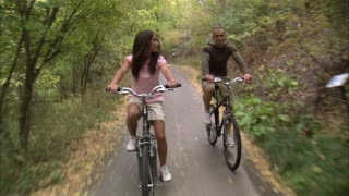 Couple Riding Bikes Through Tree Covered Path