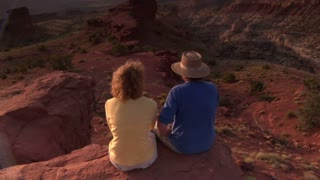 Couple Sits On A Red Rock Cliff And Admires View Capitol Reef National Park