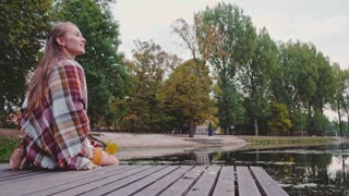 Couple sitting on a wooden jetty hugging, kissing, holding hands. 4K Ultra HD. Calm time by the autumn lake on a pier. Young man and woman in love relaxing by the lakeside. Romantic fall.