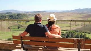 Couple sitting on bench enjoying panoramic view of Tuscany