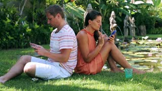 Couple sitting on grass in exotic garden and ussing cellphones
