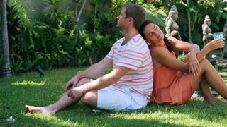 Couple sitting on grass in exotic garden next to pond and talking