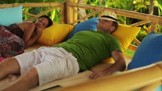 Couple sleeping on bed in the garden, steadycam shot