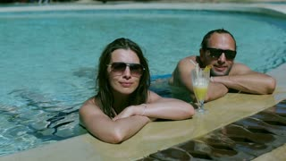 Couple smiling to the camera in the swimming pool, steadycam shot