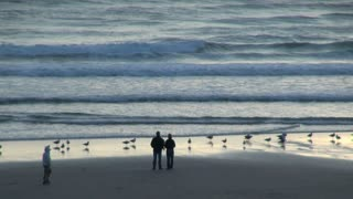 Couple Standing at Waters Edge on Cannon Beach