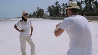 Couple taking photo on the beach, steadycam shot