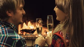Couple toasting with champangne and kissing by the fireplace. Romantic cozy night by the fireplace. Back view. 4k graded from RAW, UHD, Ultra HD resolution.