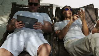 Couple using modern technology on sunbeds, steadycam shot