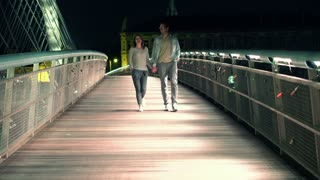 Couple walking holding hands on bridge in the night