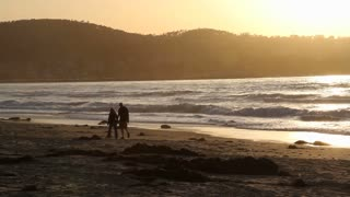 Couple Walks On Ocean Beach At Sunset