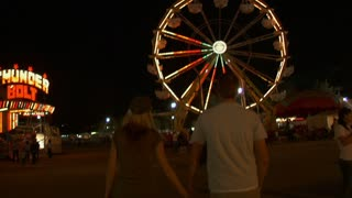 Couple Walks Through Carnival Near Ferris Wheel